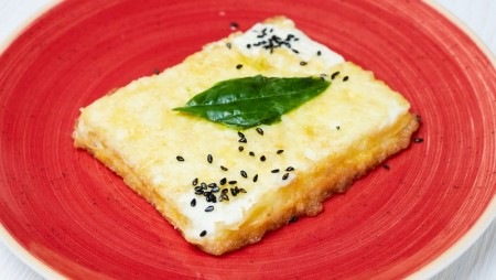 Fried feta cheese with basilico leaves.