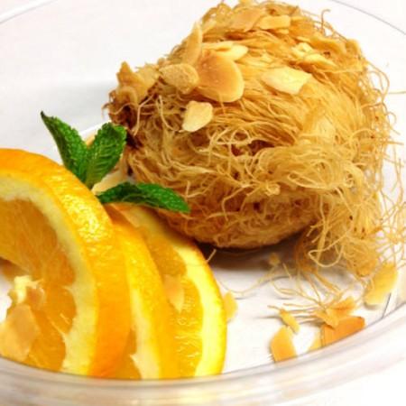 Dióval, mandulával töltött keleti csemege, friss narancsszeletekkel tálalva.