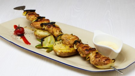 Cured chicken breast on the spit with oven baked potatoes with rosemary and cheese on top, served with dip sauce.