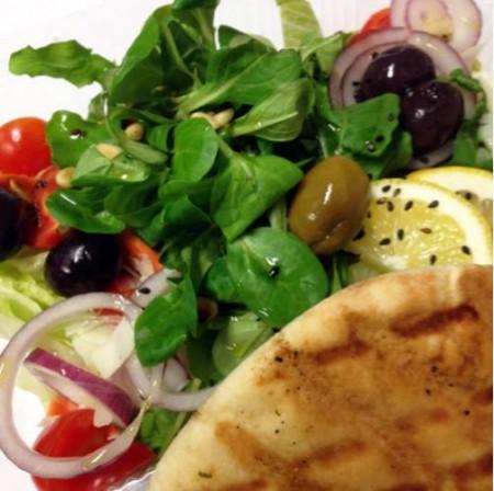 Friss zöldsaláta, zellerszár, édeskömény, hagyma, paradicsom és sárgarépa, citromos olivaöntettel, olajbogyóval,  pirított olajos magvakkal , kratsanistóval és reszelt sajttal megszórva.