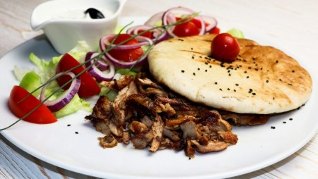 Spicy chicken meat snacks sliced from the spit with tzatziki and pita bread.